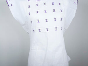 Front view Traditional handmade Mexican embroidered white blouse made of cotton on a mannequin