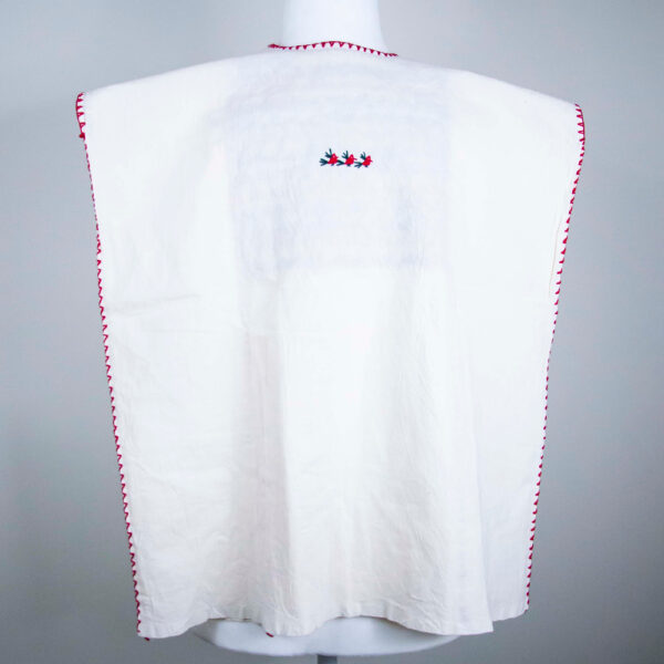 Traditional handmade Mexican embroidered white blouse made of cotton on a mannequin back view